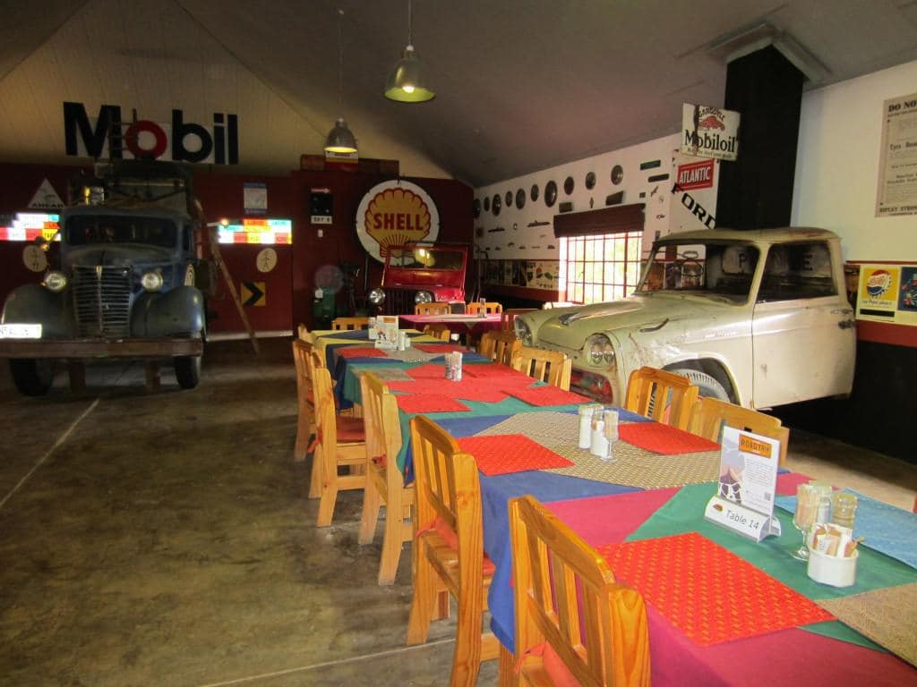 The tables of the restaurant are scattered between old cars.