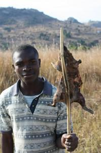 A man selling a fried rat next to the road.