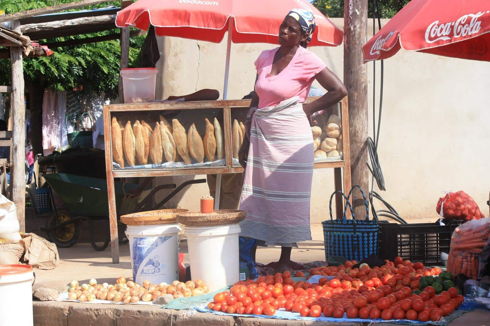 Women selling tomatoes and bread next to the road.