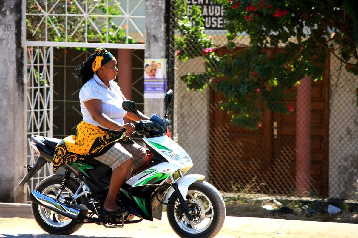 Neatly dressed women drive their own motorbikes in Mocuba.