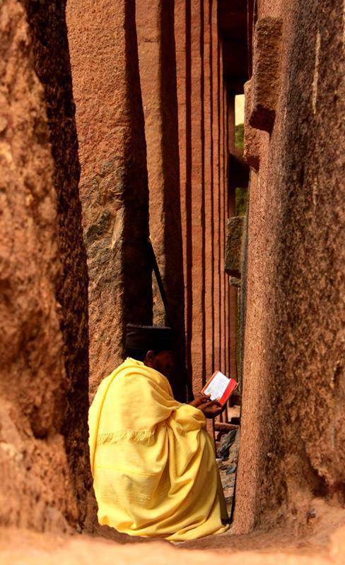 A priest, sitting face to the wall of one of the churches, reading the bible.