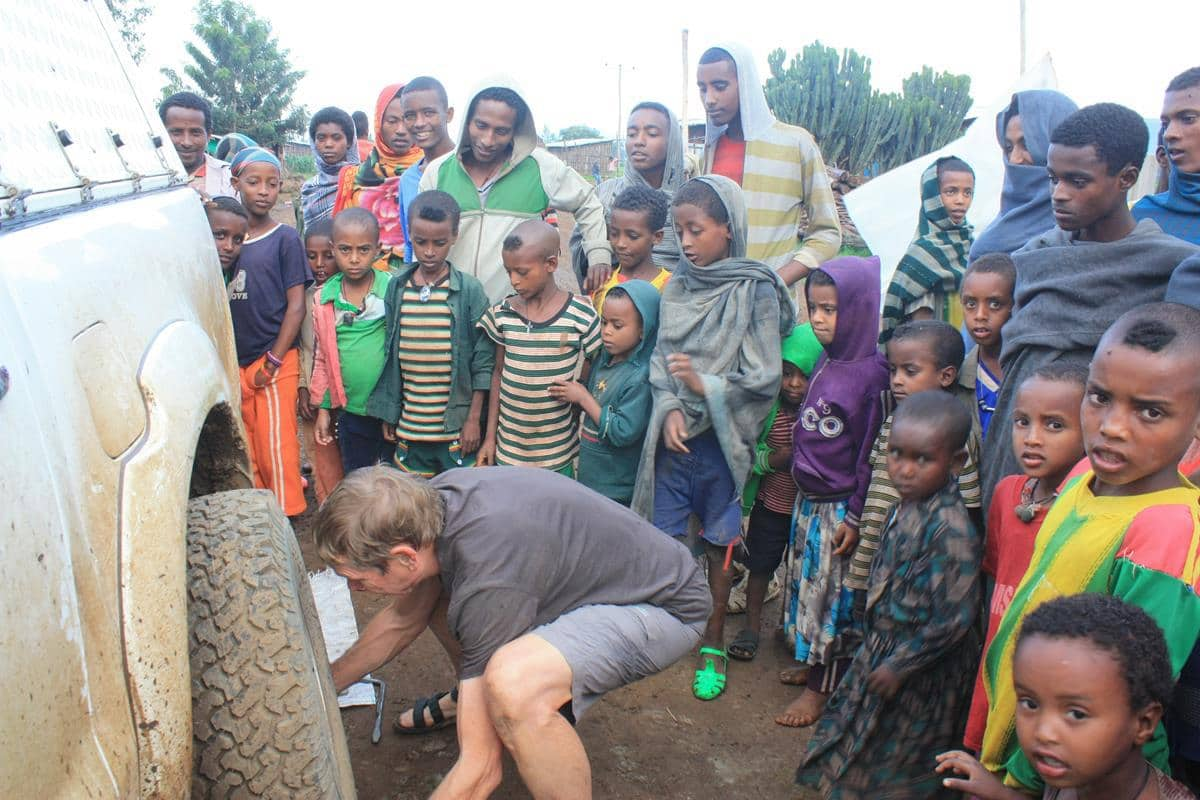 Changing a tyre with a pressing crowd of onlookers is no easy task.