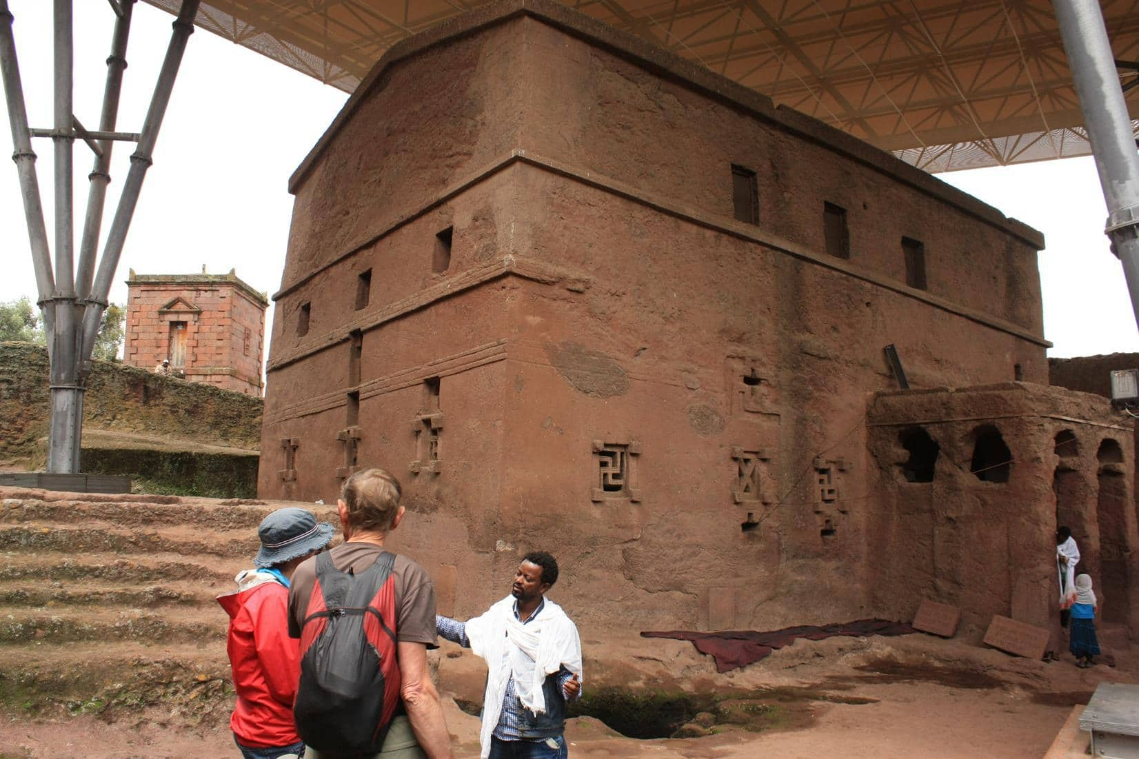 A guide explaining the architecture of one of the Lalibela churches.