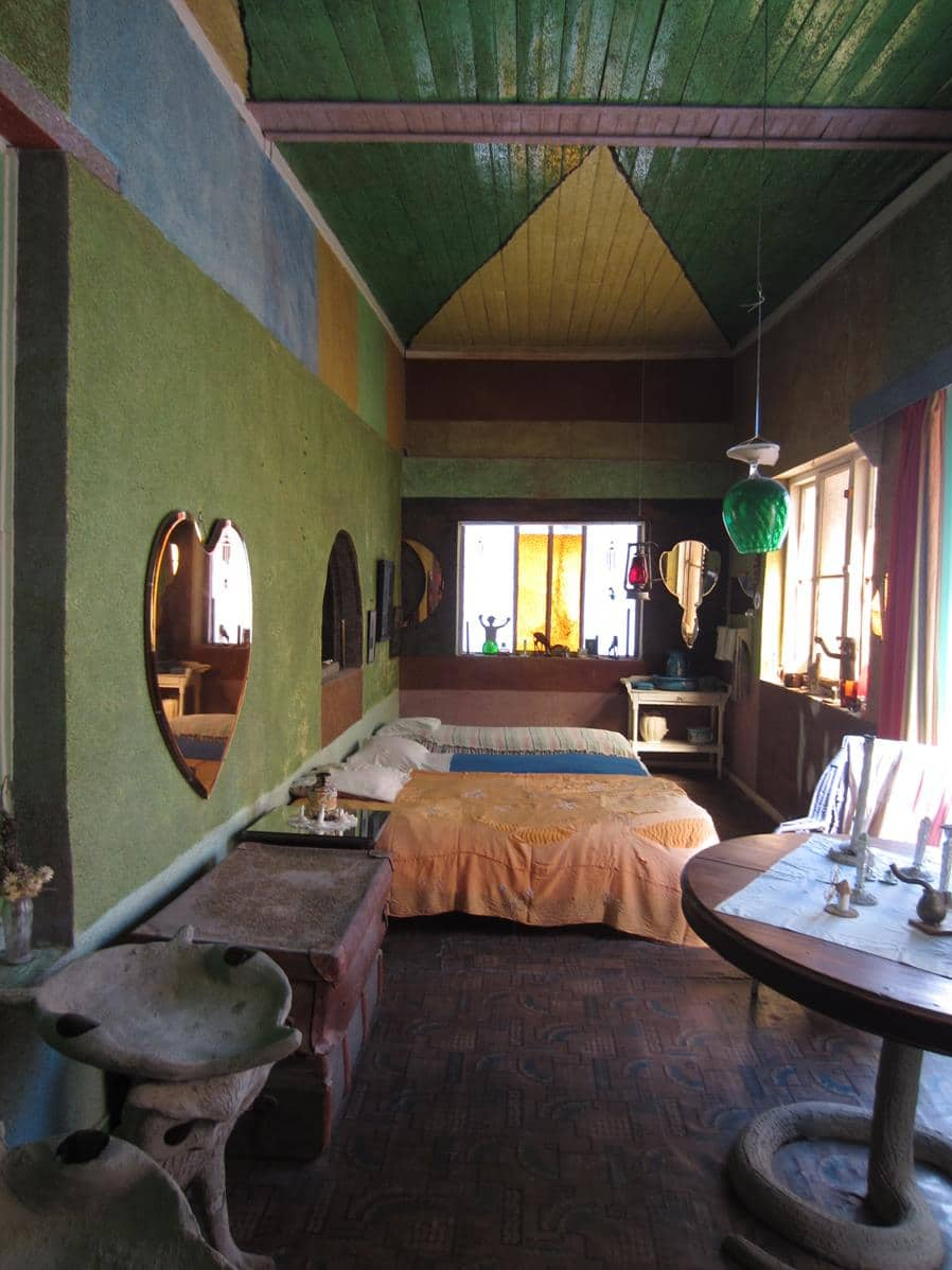 One of the bedrooms with a brightly painted ceiling and walls painted with crushed glass.
