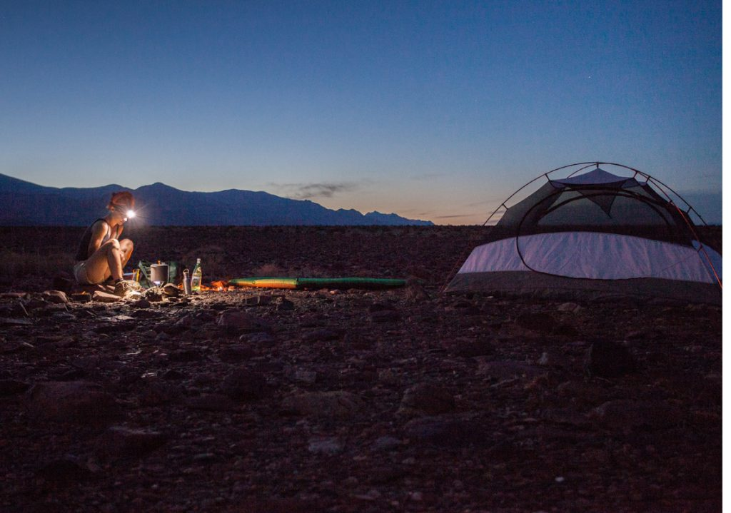 A woman uses a headlamp at her campsite